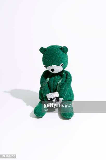 A green teddy bear holding camera