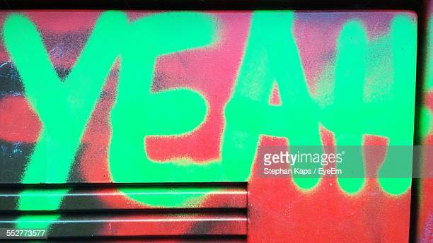 Green Text On Red Metal Wall