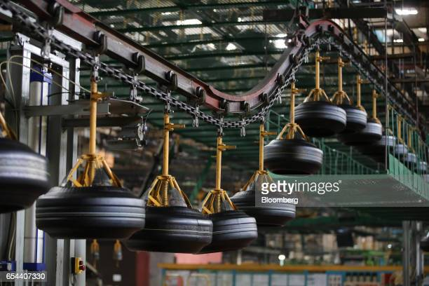'Green' tires pass along an automated conveyor belt system after shaping at the Belshina JSC tire factory in Babruysk Belarus on Thursday March 16...