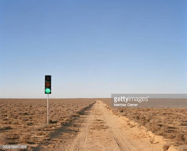 Green traffic light on desert road
