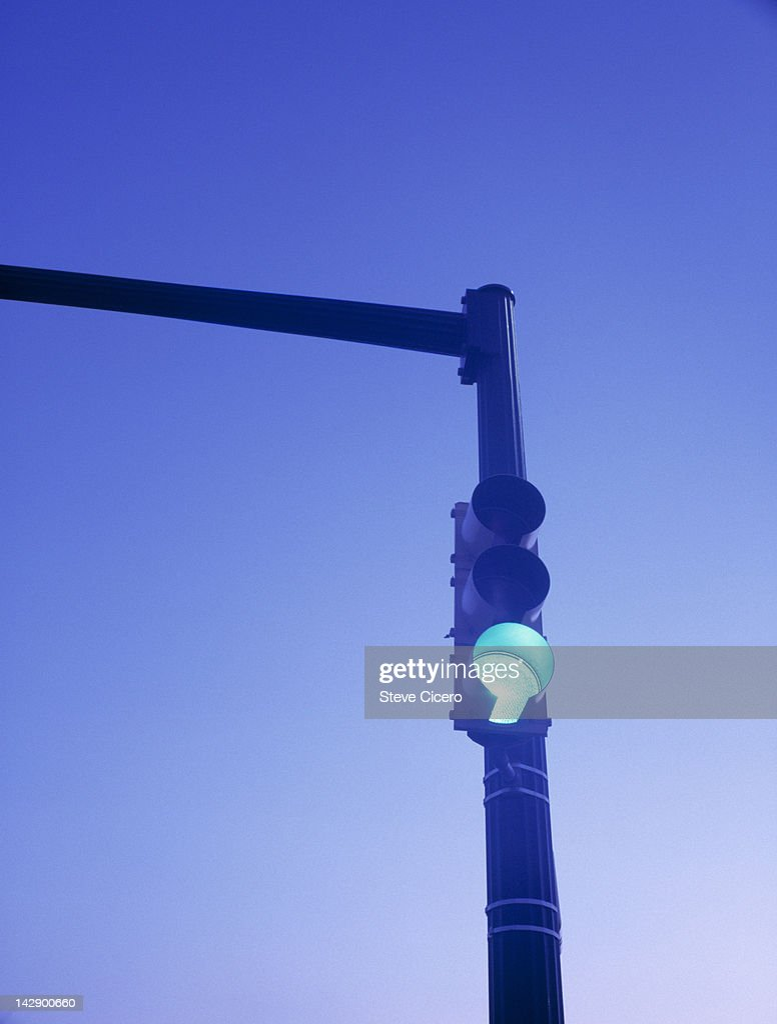Green traffic signal light at sunrise : Stock Photo