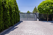 Green trees and grey entry gate to the property during summer. Real photo
