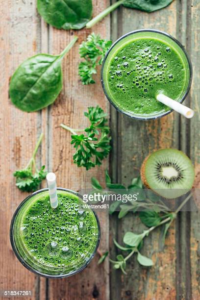 Green vegetable and fruit smoothie with spinach, salad, parsley, cress, oregano and kiwi