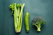 Top view of fresh green vegetables on a green background.