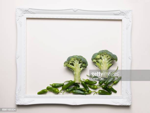 Green vegetables representing a landscape in nature in a white picture frame on a white background