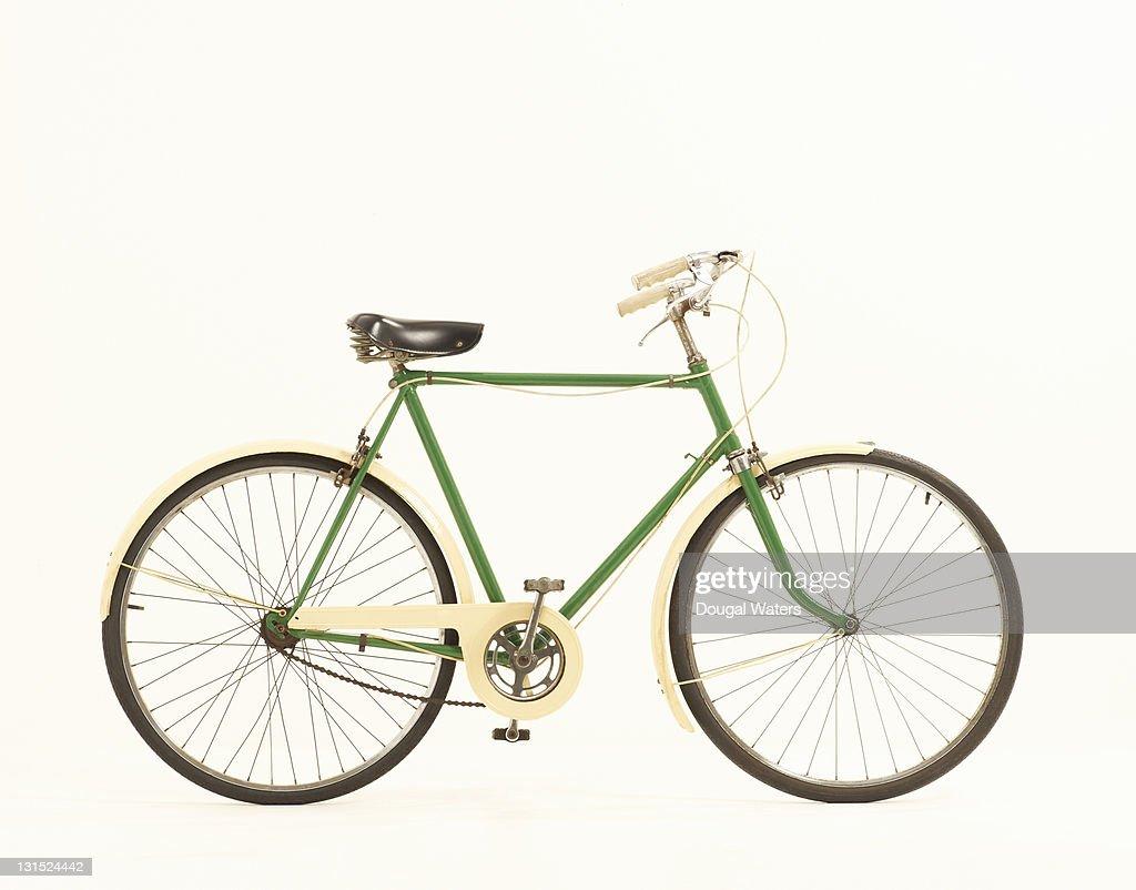 Green vintage bike against white background.