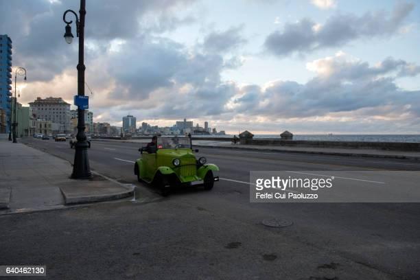 A green vintage car at street of Malecon Havana in Cuba