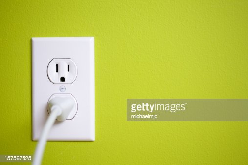 A green wall with a power socket