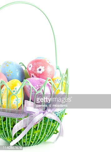 A Green Wire Easter Basket Filled with Decorated Eggs Isolated on a White Background : Stock Photo