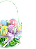 A Green Wire Easter Basket Filled with Decorated Eggs Isolated on a White Background