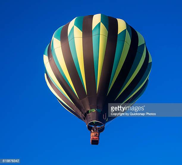 Green, yellow and black hot air balloon against a deep blue sky