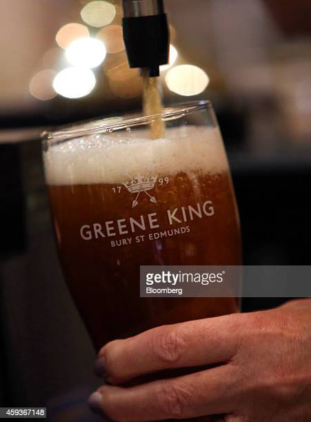 A Greene King logo sits on a pint glass as an employee pulls an 'Abbot' ale produced by Greene King Plc from a beer pump at the company's brewery in...