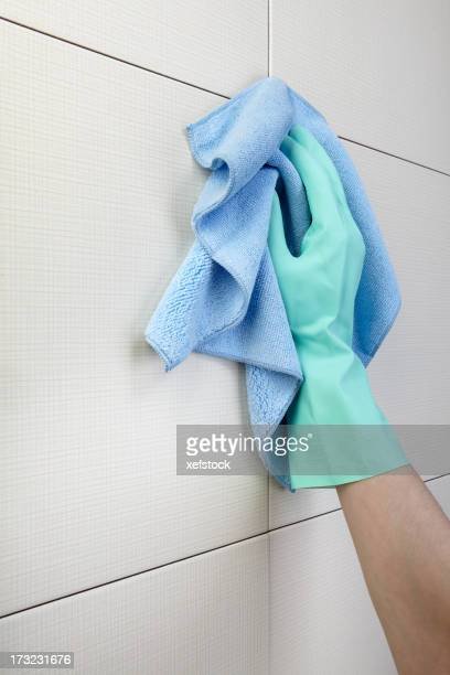 Green-gloved hand wiping shower tiles with blue cloth