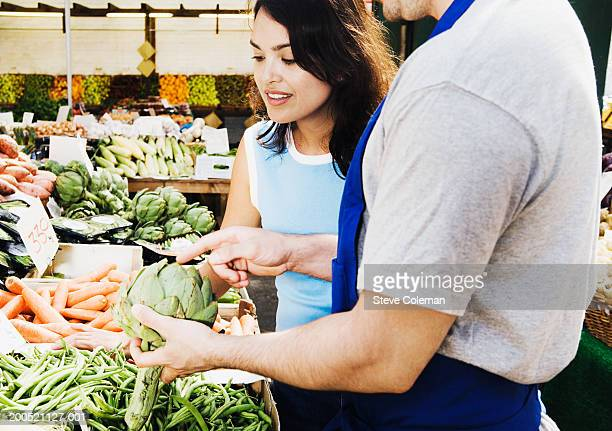 Greengrocer helping woman select vegetables at market