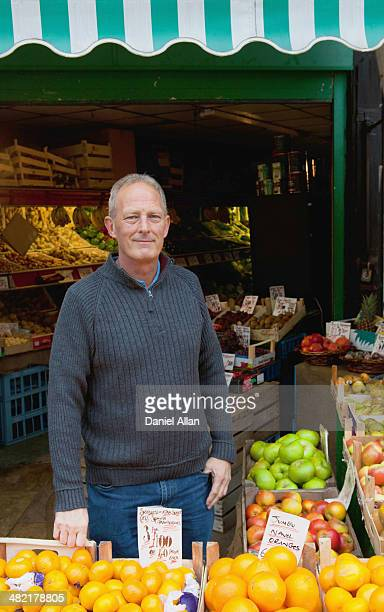 Greengrocer in front of his stall