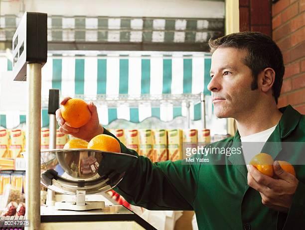Greengrocer weighing oranges.