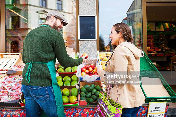Greengrocers shop, customer and grocer