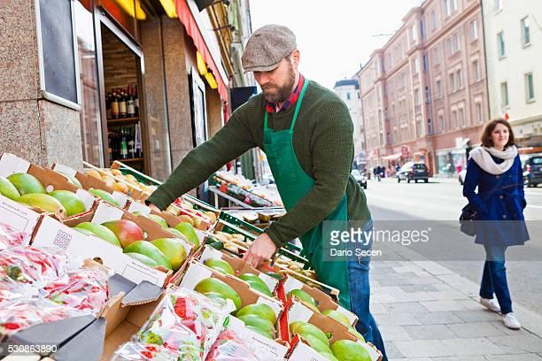 Greengrocer's shop, grocer arranging crates