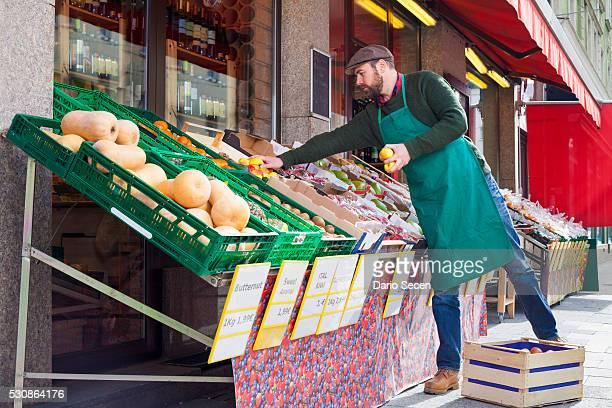 Greengrocer's shop, grocer arranging vegetables and fruit
