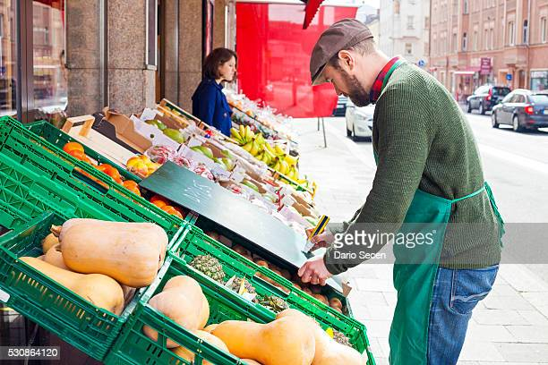 Greengrocer's shop, grocer writing price tag