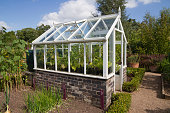 Small wooden greenhouse in English vegetable garden