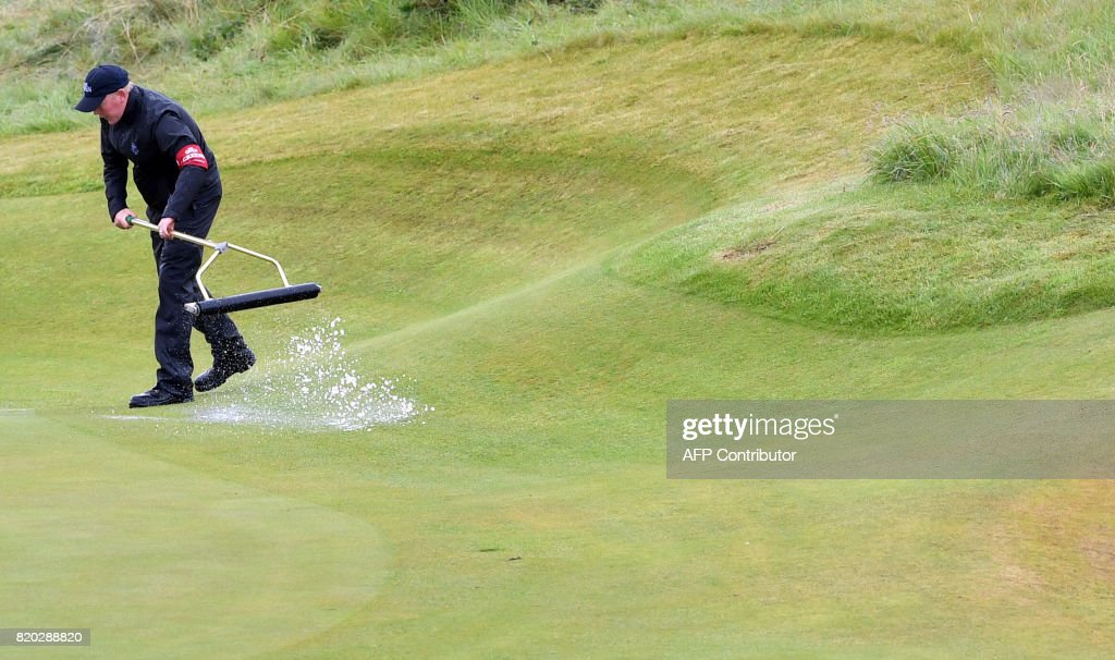 A greenkeeper uses a squeegee on the 8th green to remove standing water on day two of the Open Golf Championship at Royal Birkdale golf course near Southport in north west England on July 21, 2017. / AFP PHOTO / Ben STANSALL / RESTRICTED