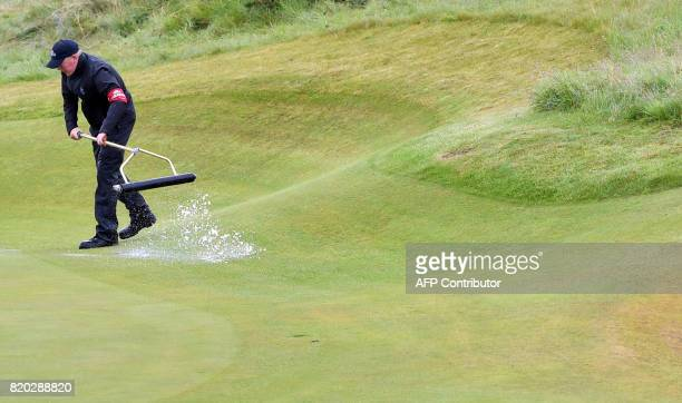 A greenkeeper uses a squeegee on the 8th green to remove standing water on day two of the Open Golf Championship at Royal Birkdale golf course near...