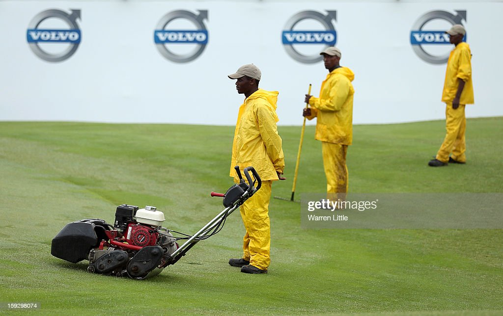 Greenkeepers look on from the 18th green as they tend to the course after heavy rain delays the start of the second round of the Volvo Golf Champions at Durban Country Club on January 11, 2013 in Durban, South Africa.