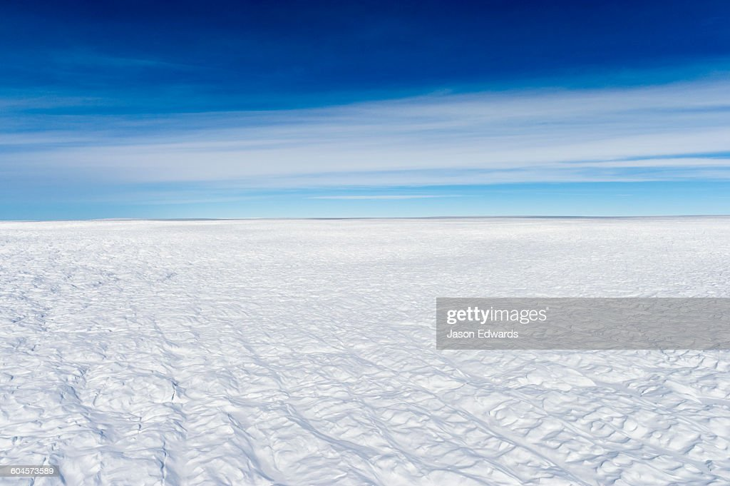 Layers of snow mask deep crevasse on the surface of the vast Greenland Ice Sheet plain.