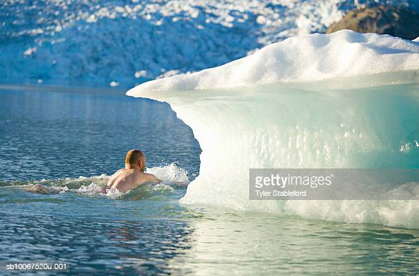 Greenland, Tasiilaq, man swimming near iceberg in Greenland Sea