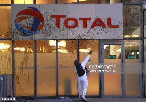 A Greenpeace activisit throws molasse on the Total logo at the French oil giant headquarters on March 27 2017 in La Defense district western Paris to...