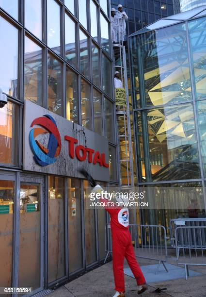 Greenpeace activisit throws molasse on Total logo at French oil giant headquarters on March 27 2017 in La Defense district western Paris to protest...