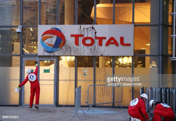 A Greenpeace activisit throws molasse on Total logo at the French oil giant headquarters on March 27 2017 in La Defense district western Paris to...