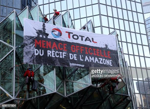 Greenpeace activisits hang a banner reading 'Total official threat of the Amazon reef' after pouring molasse in front of French oil giant Total...