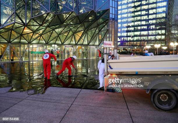 Greenpeace activisits pour molasse in front of French oil giant Total headquarters on March 27 2017 in La Defense district western Paris to protest...