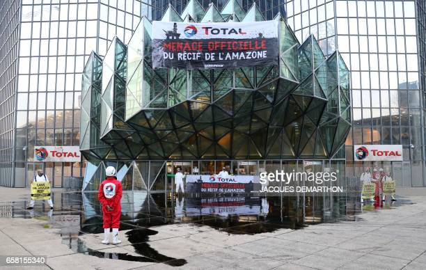 Greenpeace activisits stand after pouring molasse in front of French oil giant Total headquarters on March 27 2017 in La Defense district western...