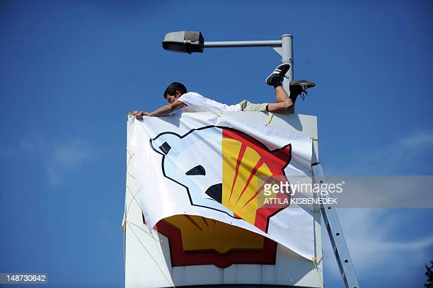 A Greenpeace activist covers the logo of a Shell petrol station in Budapest on July 19 during an action by Greenpeace's Hungarian and foreign...