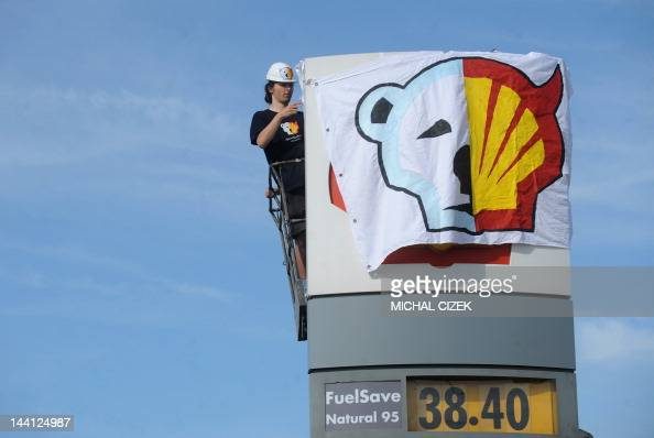 A Greenpeace activist covers the logo of the Shell oil company to protest on May 10 2012 against the heading of the an icebreaker for Shell's Arctic...