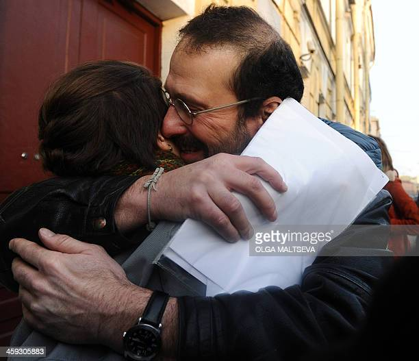 Greenpeace activist Dimitri Litvinov from Sweden hugs an unidentified person while holding papers certifying the termination of prosecution outside...