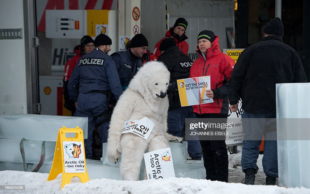 A Greenpeace activist, dressed as a polar bear, is chained onto a petrol tap at a filling station during a protest against global oil giant Shell on January 25, 2013 in Wolfgang near the Swiss resort of Davos where the 2013 World Economic Forum (WEF) is taking place.