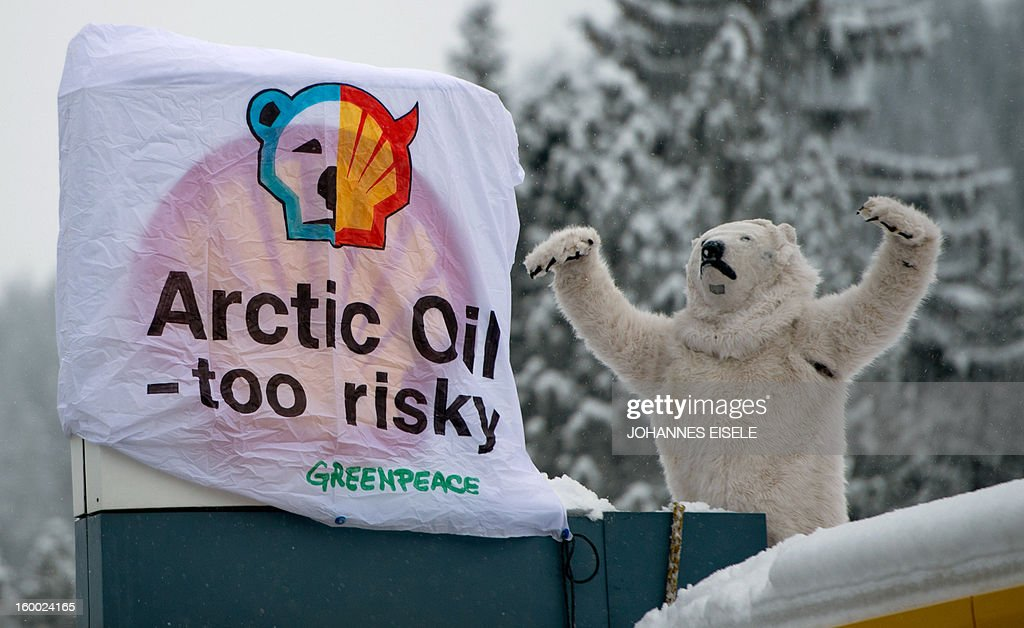 A Greenpeace activist dressed as a polar bear stand on the roof of a filling station during a protest against global oil giant Shell on January 25, 2013 in Wolfgang near the Swiss resort of Davos where the 2013 World Economic Forum (WEF) is taking place. AFP PHOTO / JOHANNES EISELE