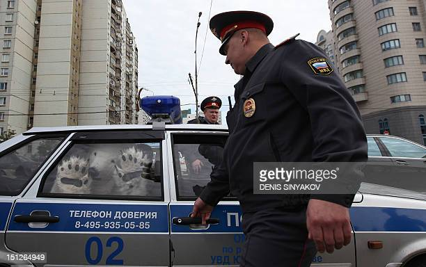 A Greenpeace activist dressed as polar bear sits in a police car in Moscow on September 5 after he was detained while protesting against oil drilling...