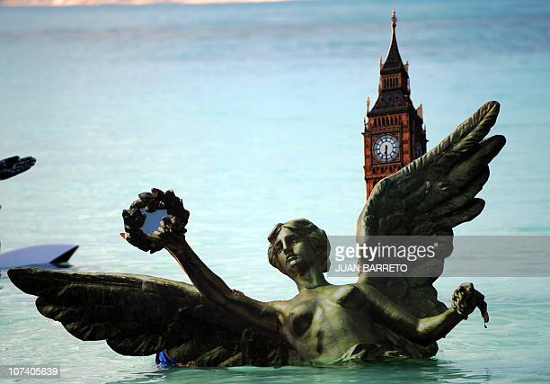 A Greenpeace activist holds a figure of Mexico's Angel of Independence during their symbolic 'Sinking Icons' activity by submerging icons of world...