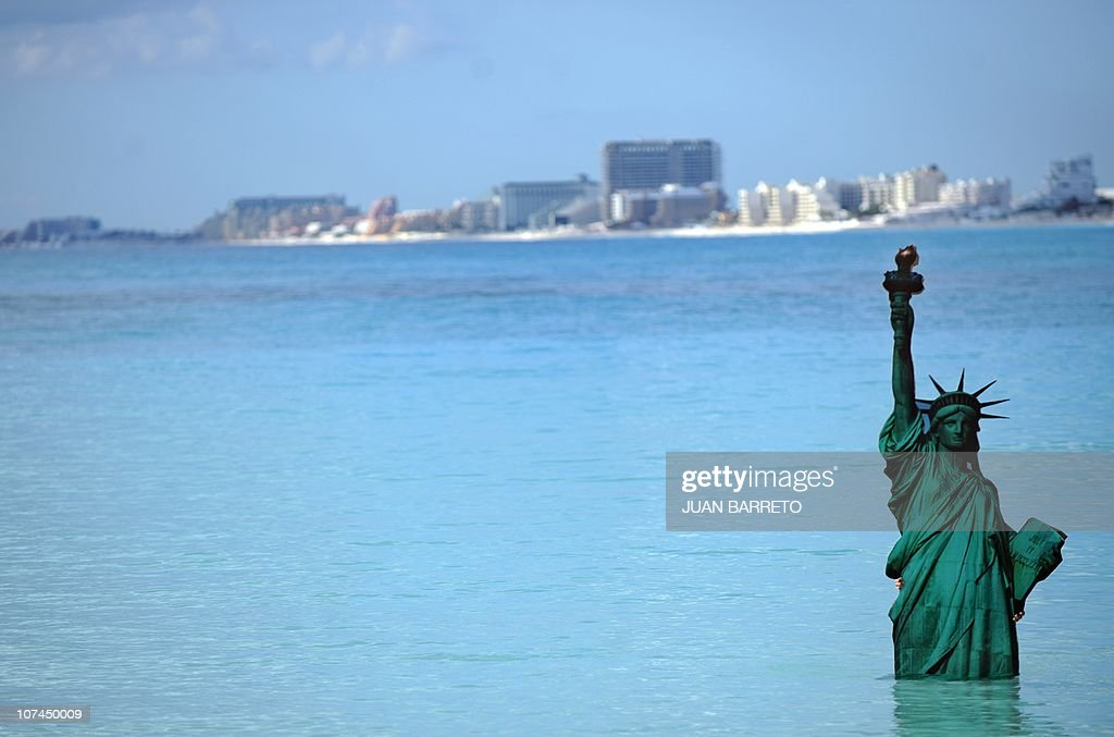 A Greenpeace activist holds a figure of the US Statue of Liberty during their symbolic 'Sinking Icons' activity by submerging icons of world famous...