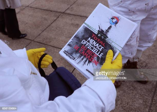 A Greenpeace activist holds a leaftet reading 'Total official threat of the Amazon reef' after pouring molasse in front of French oil giant Total...