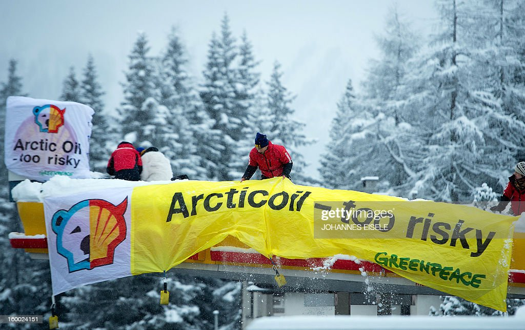 A Greenpeace activist installs a Banner on a roof of a filling station during a protest against global oil giant Shell on January 25, 2013 in Wolfgang near the Swiss resort of Davos where the 2013 World Economic Forum (WEF) is taking place. AFP PHOTO / JOHANNES EISELE