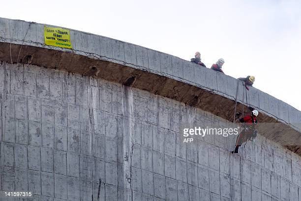 A Greenpeace activist is suspended from the cooling tower of Turow Power Station in Bogatynia on March 19 2012 Greenpeace activists scaled a 100metre...