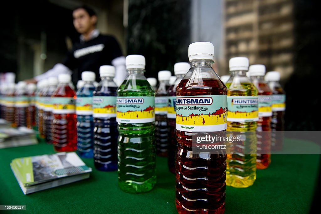 A Greenpeace activist prepares to distribute coloured water bottles labeled 'Huntsman-Santiago water', during a protest at the World Trade Center against Huntsman Corporation on November 15, 2012 in Mexico City. According to a statement distributed by Greenpeace, Huntsman, one of the largest suppliers of chemicals for the textile sector globally, discharges pollutants into the Rio Santiago in Jalisco, Guadalajara, which affect the human health and the aquatic ecosystem.