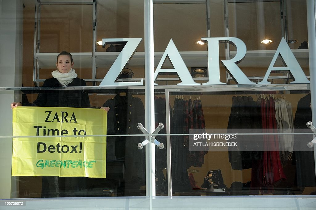 A Greenpeace activist stands with her banner in the window of Zara's fashion shop in Budapest on November 20, 2012 during a demonstration. High street fashion brands are selling clothing contaminated with hazardous chemicals that break down to form hormone-disrupring or even cancer-causing chemicals when released into the emviroment, according to report released today by Greenpece International. AFP PHOTO / ATTILA KISBENEDEK