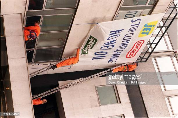 Greenpeace activists attach a banner to the walls of Conoco Oil's offices in central London today in protest against their plans for oil exploration...
